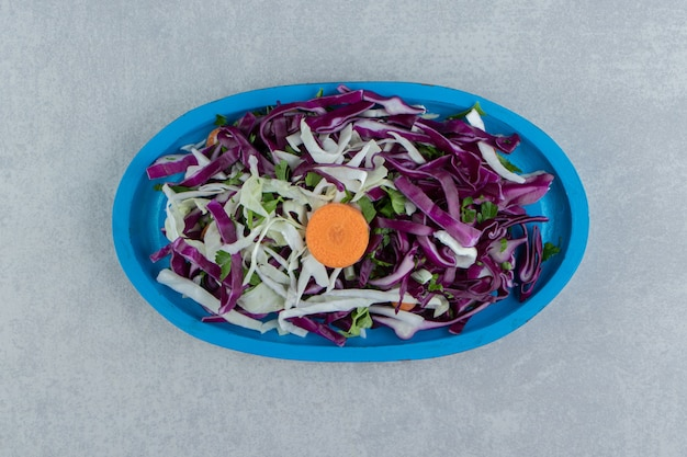 Chopped cabbage and greens in wooden plate, on the marble background.