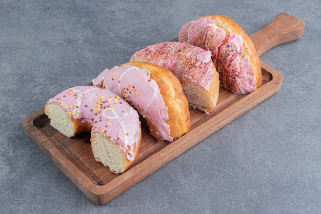 Chopped cake with pink frosting on a wooden board