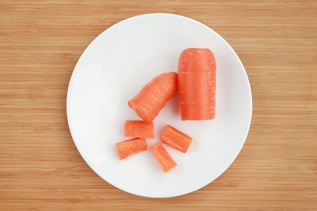 Chopped carrot on white plate against wooden board.