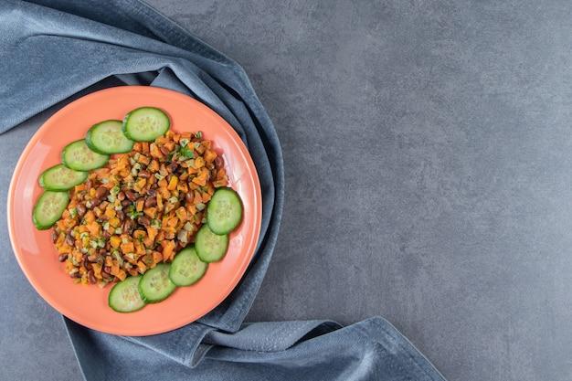 Нарезанная морковь, фасоль и огурец на тарелке на полотенце рядом с целой морковью на мраморной поверхности