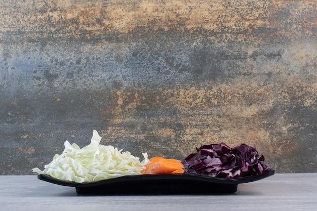 Нарезанная морковь, красная и белая капуста на черной тарелке. фото высокого качества
