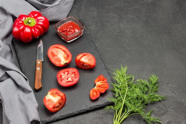 刻んだセロリの茎、グリーントマト、グレープレートのディル。包丁。スペースをコピーします。黒の背景。上面図