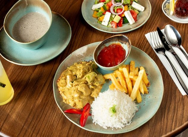 Chopped chicken breast prepared with sauce and served with rice, french fries, ketchup, salad and soup