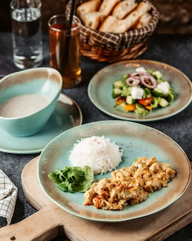 Chopped chicken breast prepared with sauce and served with rice salad and soup