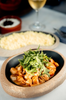 Chopped chicken breast in sauce and arugula