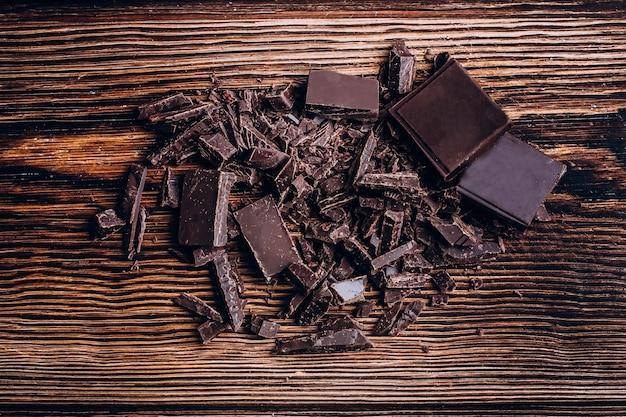 Chopped chocolate bar on wooden table background.