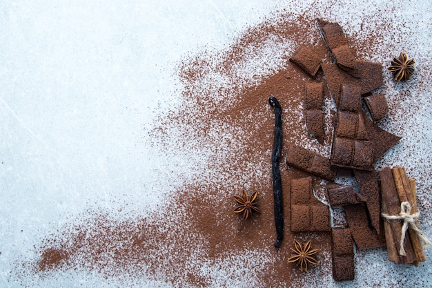 Chopped chocolate with cocoa, cinnamon and vanilla stick