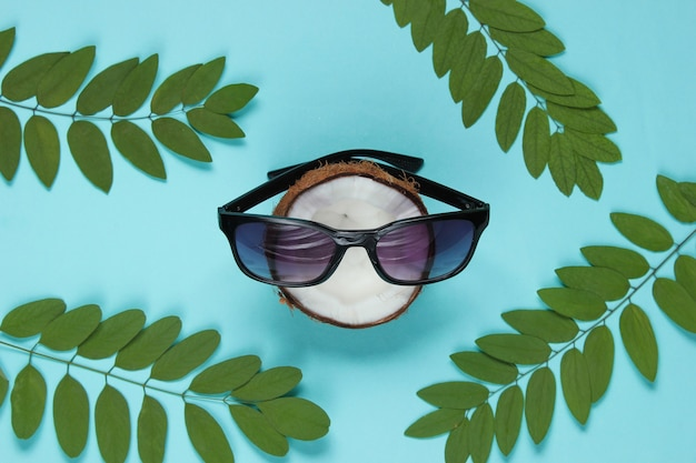 Chopped coconut with sunglasses on blue background with green leaves