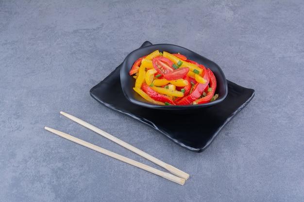 Insalata di peperoni colorati tritati in un piatto di legno