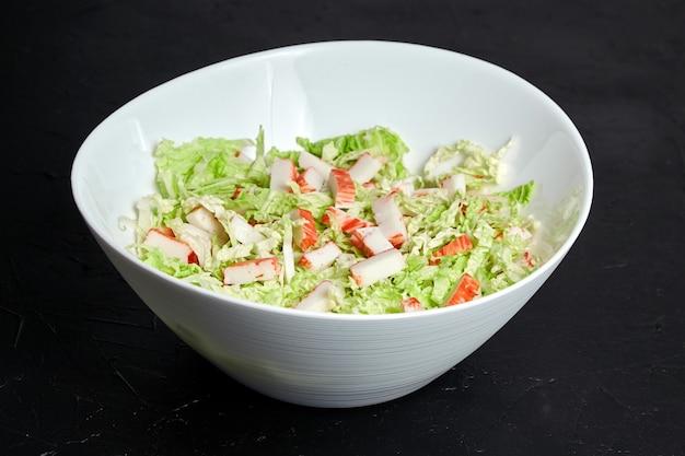 黒い石のテーブルの上の白いセラミックボウルに刻んだカニカマと新鮮な白菜の葉