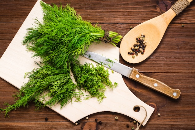 Chopped fresh dill on a cutting board and a bunch of dill on a wood table. top view