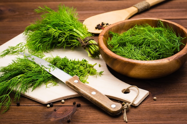 Chopped fresh dill on a cutting board and dill in a wood bowl on the table