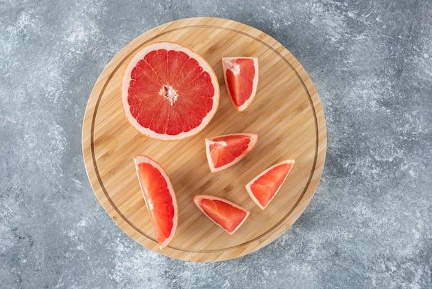 木製の丸い板の上に置かれたみじん切りの新鮮な酸っぱいグレープフルーツ。
