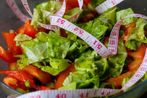 菜食主義の女の子のための皿に刻んだ新鮮な野菜サラダ