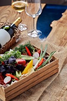 흰색 바탕에 나무 상자에 다진된 신선한 야채. 연회 축제 요리. 미식식당 메뉴판.