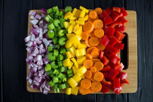 黒の木製の背景にまな板でみじん切りの新鮮な野菜。