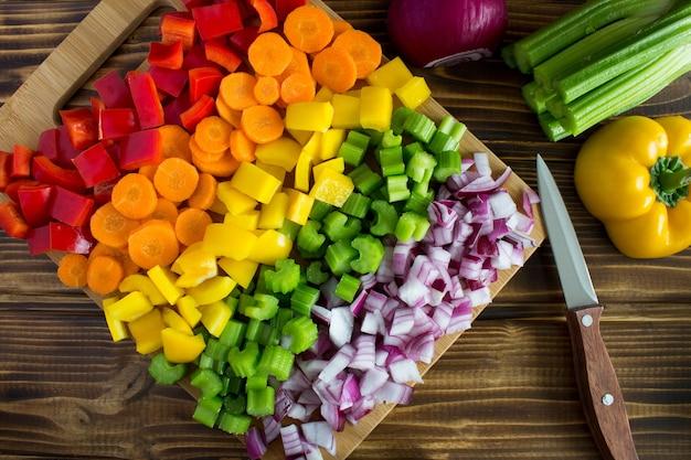茶色の木のまな板でみじん切りの新鮮な野菜