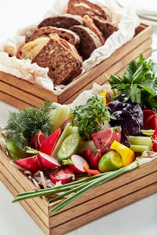 Chopped fresh vegetables in a wooden box on a white surface