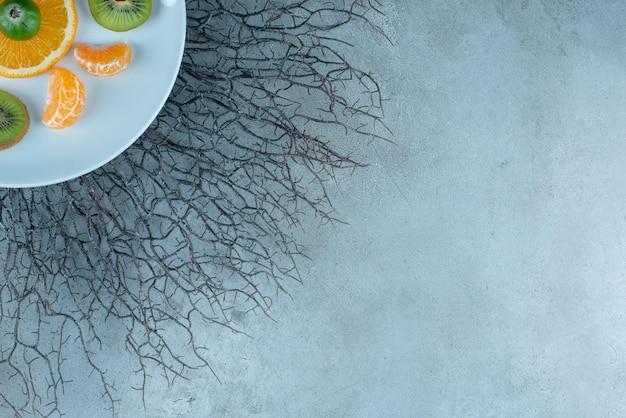 Macedonia di frutta tritata in un piatto di ceramica su cemento.