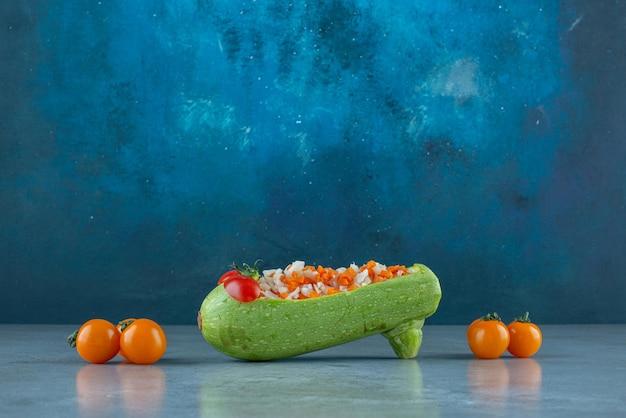 Insalata di frutta e verdura tritata all'interno di una zucchina intagliata.