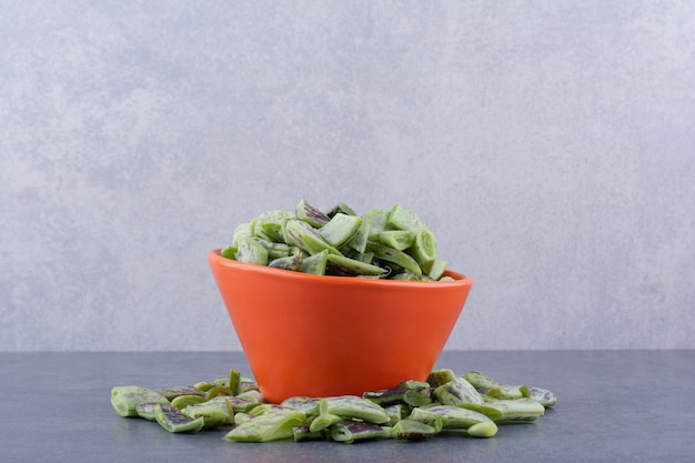 Chopped green beans inside a cup on blue surface