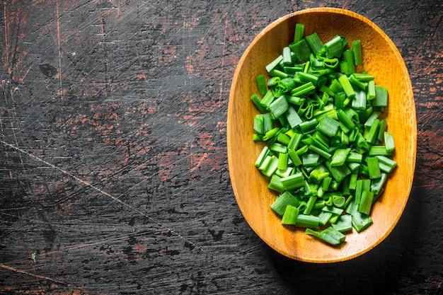 Нарезанный зеленый лук в деревянной тарелке на черном деревенском столе