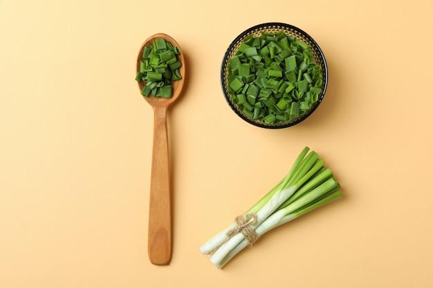 Нарезанный зеленый лук ложкой и миской на бежевом