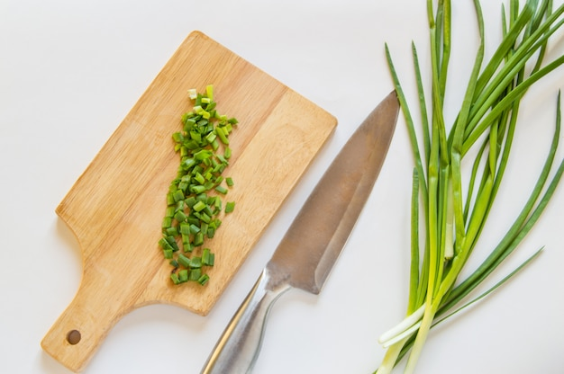 Chopped green onion on wooden board, knife on white isolated background