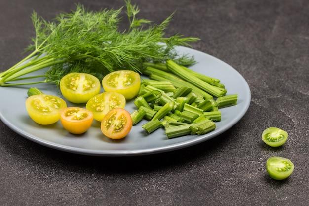 みじん切りのグリーントマト、みじん切りのセロリの茎、灰色の皿にディルの小枝。黒の背景。上面図