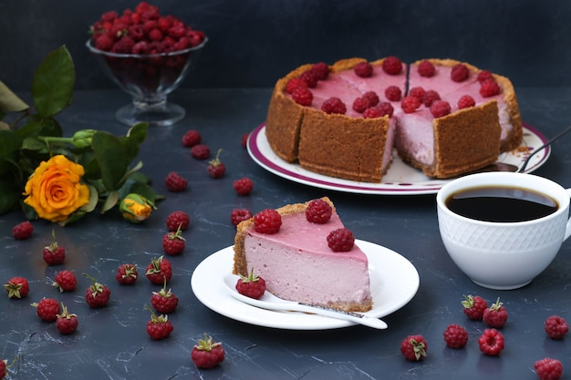 Chopped homemade raspberry cheesecake in portions on a plate, located on dark surface, horizontal format