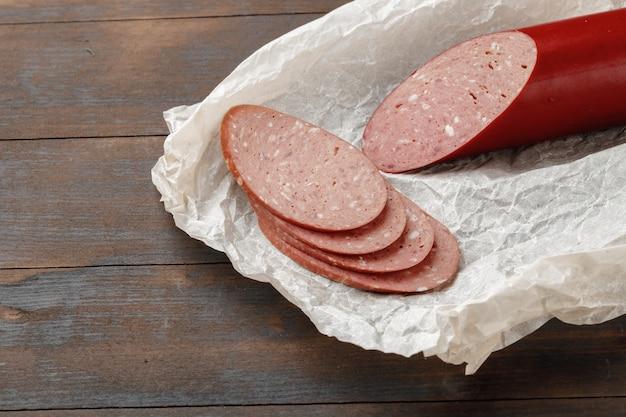 Колбаса из рубленого мяса на деревянной доске крупным планом