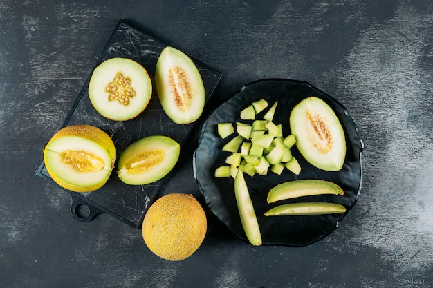 Chopped melon in a black bowl with split in half melon flat lay on a dark wooden background