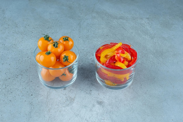 Chopped multicolor bell peppers in a glass cup.