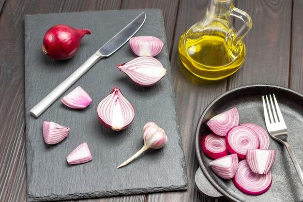 まな板に刻んだ玉ねぎとナイフ。フライパンに紫玉ねぎとフォークをスライスしました。オリーブオイルのボトル。暗い木の背景。上面図