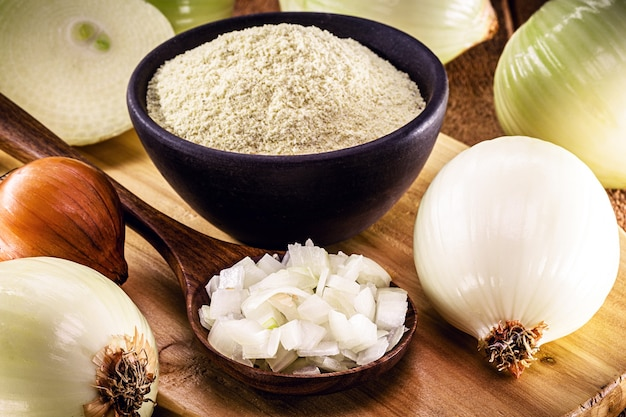 Chopped onion in wooden spoon with powdered onion pot in the background
