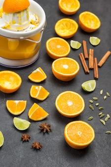 Нарезанные апельсины и палочки корицы на столе. соковыжималка с апельсиновой цедрой. черный фон. вид сверху