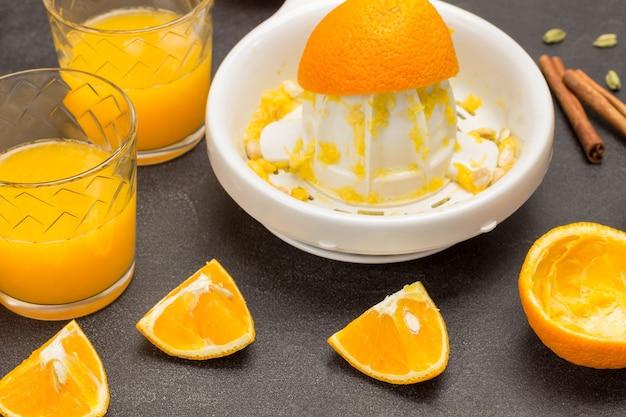 Нарезанные апельсины на столе. два стакана апельсинового сока. цедра апельсина на соковыжималке. черный фон. вид сверху
