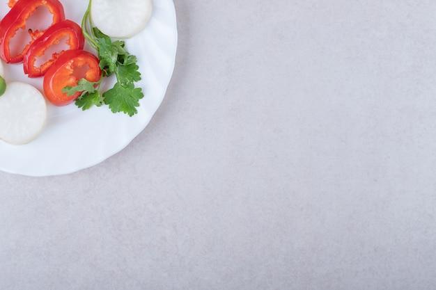 Нарезанные петрушку и перец на тарелке, на мраморе.