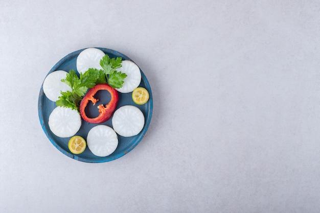 대리석 위에 다진 파슬리, 무, 후추, 금귤을 나무 접시에.