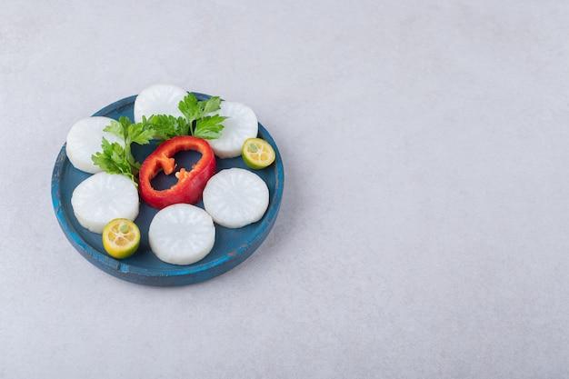 Chopped parsley, radish, pepper, kumquat on wooden plate on marble table.