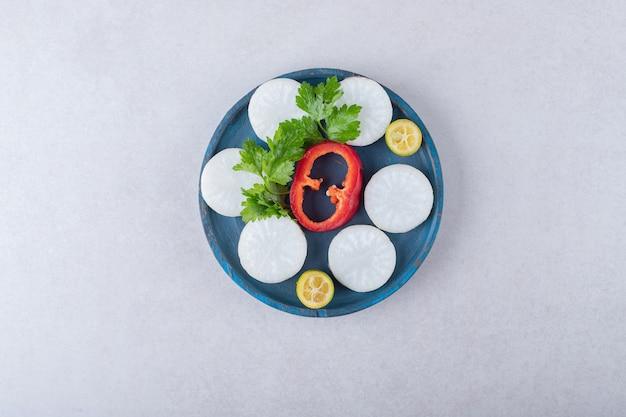 Prezzemolo tritato, ravanello, pepe, kumquat sul piatto di legno, sul marmo.