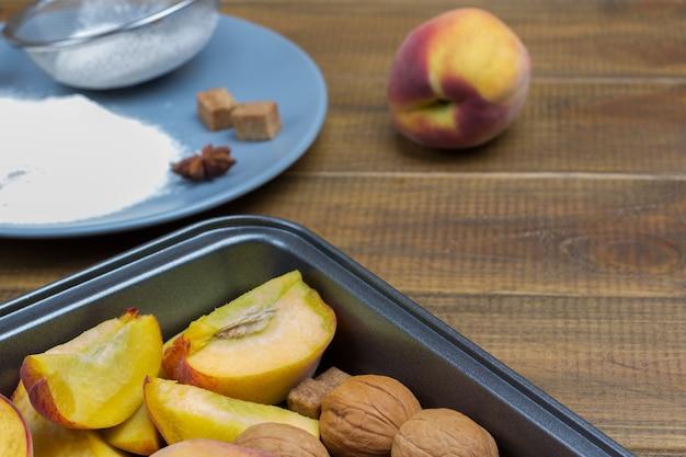 天板に刻んだ桃とクルミ。ふるいと小麦粉を皿にのせます。スペースをコピーします。木製の背景。上面図