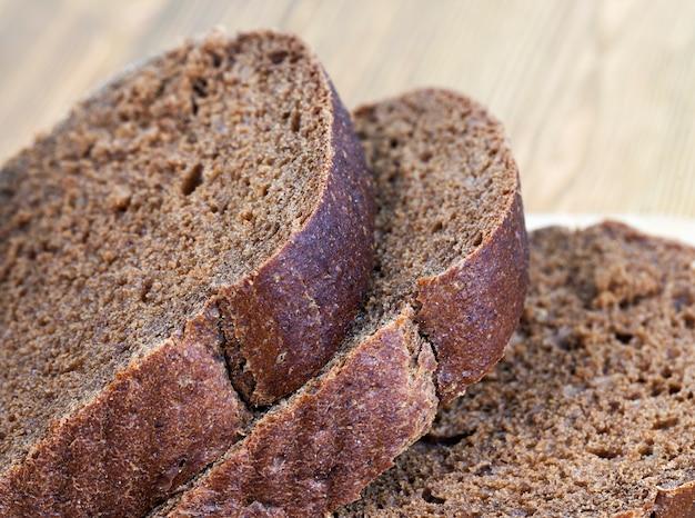 Нарезанные кусочки черного свежего хлеба на световой доске