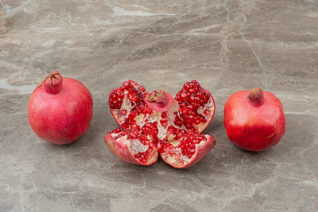 Chopped pomegranates and seeds on marble table