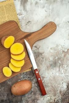 混合色の背景に古い新聞の木製まな板に刻んだジャガイモ
