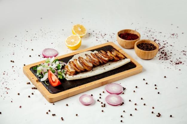 Patate tritate con grasso e cipolle su una tavola di legno