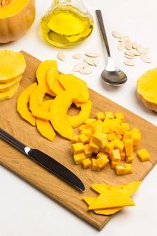 まな板に刻んだカボチャとナイフ。テーブルの上の油、種子、スプーン。上面図。白色の背景