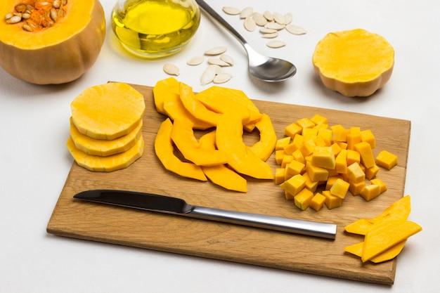 まな板に刻んだカボチャとナイフ。種とカボチャ。テーブルの上の油、種子、スプーン。上面図。白色の背景