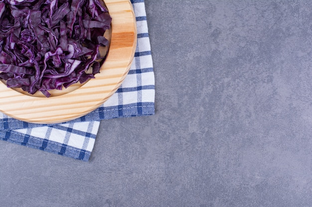 Cavolo viola tritato su un piatto di legno.