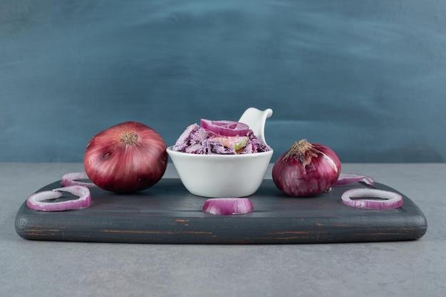 세라믹 컵에 다진 보라색 양파와 양배추 샐러드.